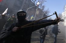 A protester uses a slingshot during clashes with police in Kiev