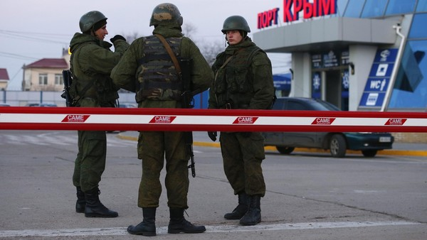 Armed men, believed to be Russian soldiers, stand outside the civilian port in the Crimean town of Kerch. Russia started a build up of armored vehicles on the Russian side of a narrow stretch of water between Russia and the Ukrainian region of Crimea, Ukrainian border guards said.