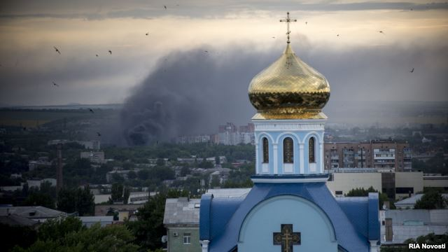 Smoke rises after an artillery attack in the city of Luhansk. Photo source:  http://www.rferl.org/content/ukraine-luhansk-republic-border-crossing-russia/25463115.html
