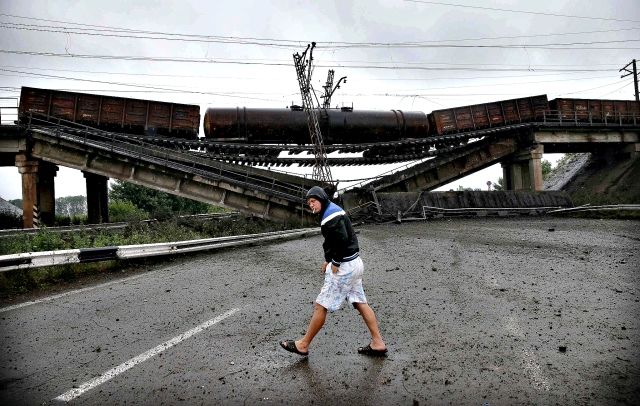Man walking past the destroyed railroad bridge which fell over a main road leading to Donetsk, near the village of Novobakhmutivka.  REUTERS/Maxim Zmeyev