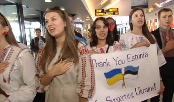 Ukrainian students sing the national anthem in the airport after having arrived in Estonia