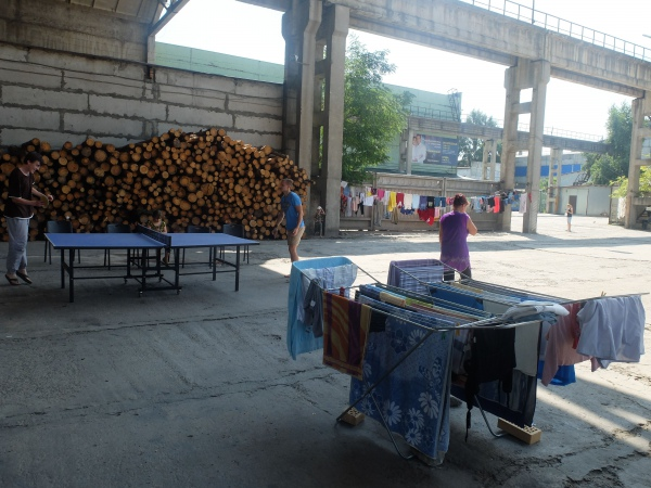 Firewood is stacked by the wall, while laundry dries in the courtyard