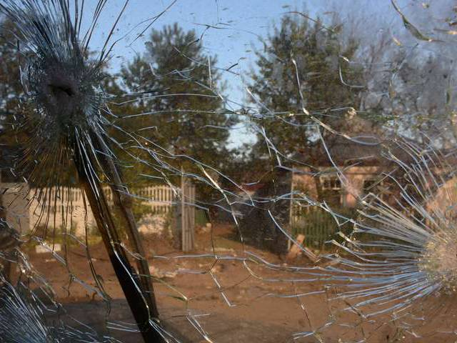 Photo taken through the damaged windshield of a vehicle in Donetsk's Oktyabrsky district, adjoining the airport,on  October 2, 2014. AFP PHOTO / JOHN MACDOUGALL