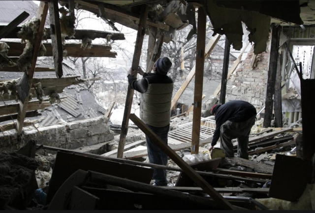 Local residents remove debris at a house damaged by recent shelling in Donetsk, eastern Ukraine, January 21, 2015. REUTERS/Alexander Ermochenko
