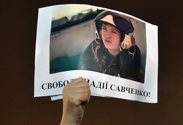 "A demonstrator holds aloft a picture of Ukranian army officer captured by pro-Russian insurgents, Nadiya Savchenko , bearing the slogan ""Free Nadiya Savchenko"" during a rally on Independence Square in Kiev on January 26, 2015 demanding her liberation during an International day of support for her. The first lieutenant of the Ukrainian airforce, helicopter pilot Nadiya Savchenko was fighting in a Ukrainian volunteer battalion in east of the country and captured by pro-Russian insurgents in eastern Ukraine, later handed over to Russia, and charged with the killing of two Russian journalists during the 2014 insurgency in Donbass. AFP PHOTO/ SERGEI SUPINSKY"