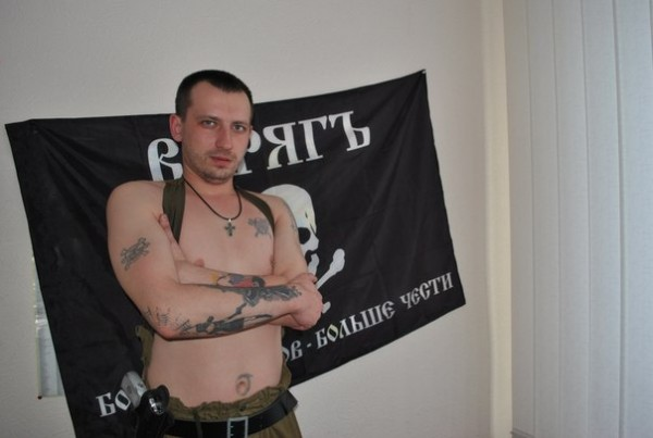 Matyushin posing with the Varyag squad flag. The motto reads: More enemies - more honor.