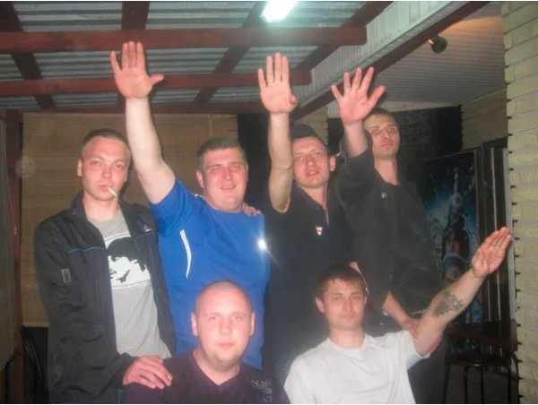 "Alexander ""de Krog"" Matyushin and friends, performing a Nazi salute. The political affiliations of the ""DNR"" founder (top row, second right) are clear without further comment."