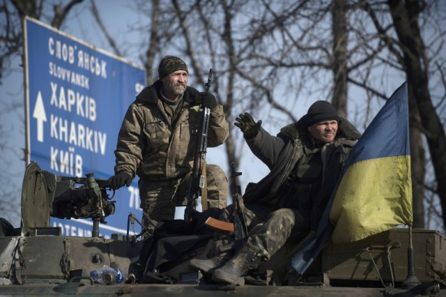 Ukrainian soldiers guard a road atop their military vehicle near Artemivsk, eastern Ukraine, Monday, Feb. 23, 2015.