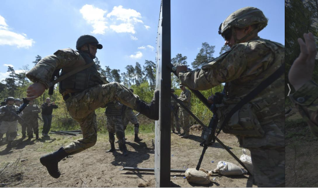 A serviceman of the U.S. Army's 173rd Airborne Brigade Combat Team (R) trains Ukrainian soldiers during a joint military exercise called 'Fearless Guardian 2015' at the military training area in Yavoriv, outside Lviv, Ukraine, May 12, 2015. REUTERS/OLEKSANDR KLYMENKO. Source.