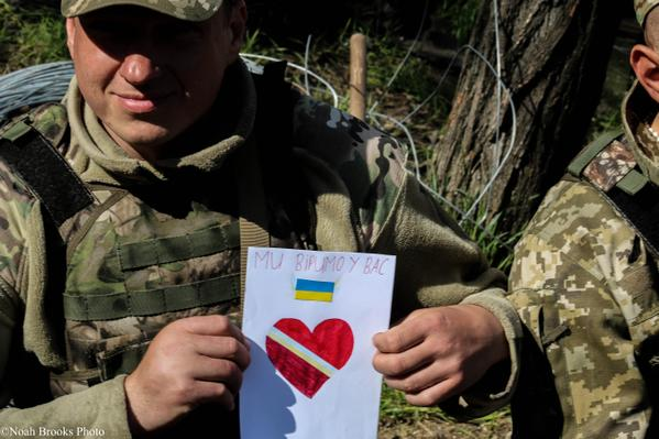 "Ukrainian soldier with letter from child that reads: ""We believe in you."" Photo: Noah Brooks. Source"
