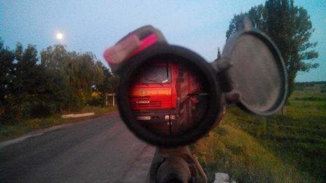 Ukrainian soldier and  sniper keeps watch through his scope at a checkpoint as full moon rises. Photo: Mykola Voronin