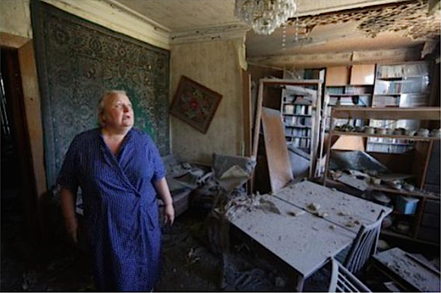 In Donetsk, a woman assesses the damages to her house from shelling on July 19, 2015. Photo: Aleksey Filippov, AFP. Source: https://twitter.com/molodyko/status/623146475032313856