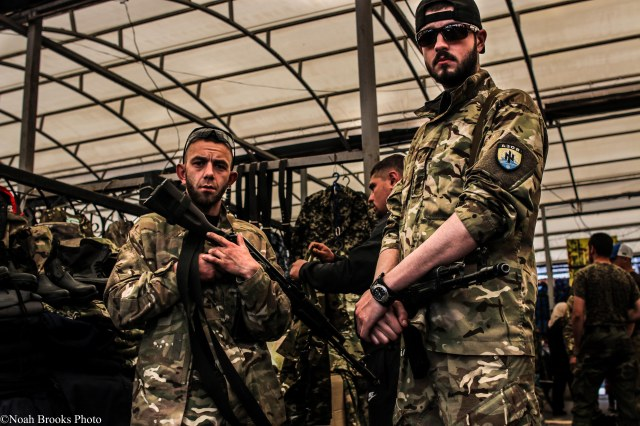 Volunteers from Azov Battalion shop for boots in Mariupol. Photo: Noah Brooks.