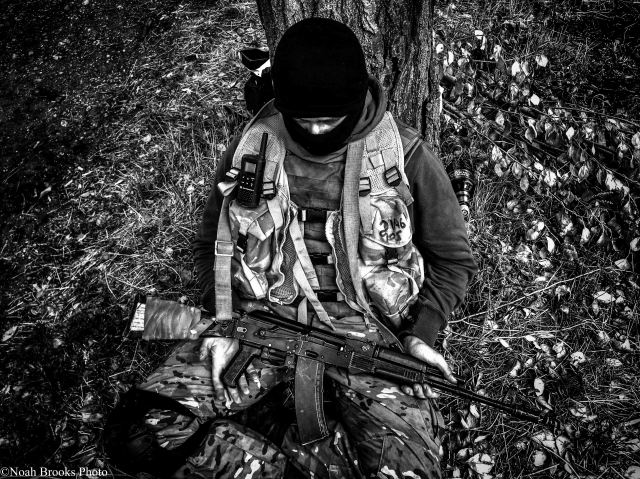 A soldier waiting at a block post behind some trees near Mariupol while continued shelling targets their position. Photo: Noah Brooks