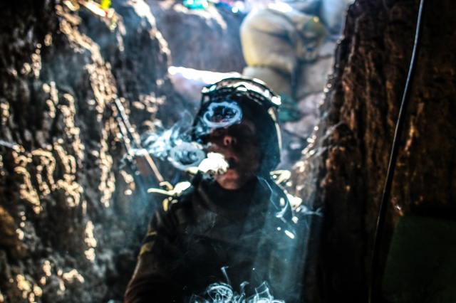 A soldier takes a smoke break after a firefight in Shyrokyne. Photo: Noah Brooks