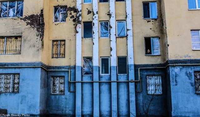 A woman looks out her apartment window where separatists killed 30 and wounded nearly 100 in a rocket attack earlier this year. Photo: Noah Brooks