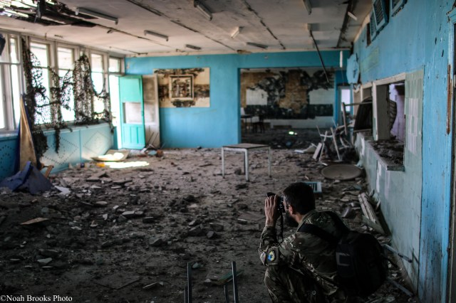 Azov photographer Ruslan photographs damage to a school. Photo: Noah Brooks