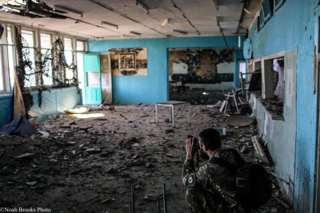 Azov photographer Ruslan photographs damage to a school. Photo: Noah Brooks