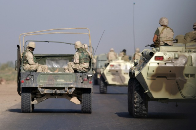 US Marine Corps Reserve (USMCR) Marines (left) assigned to Kilo/Company, 3rd Battalion, 23rd Marine Regiment (Kilo 3/23), 4th Marine Division, aboard a High-Mobility Multipurpose Wheeled Vehicle (HMMWV) and Ukrainian Army Soldiers aboard BRT-80A (8x8) armored personnel carriers (APC), travel along a highway from Al Kut to As Suwayrah, Iraq, during Operation IRAQI FREEDOM. Photo source.