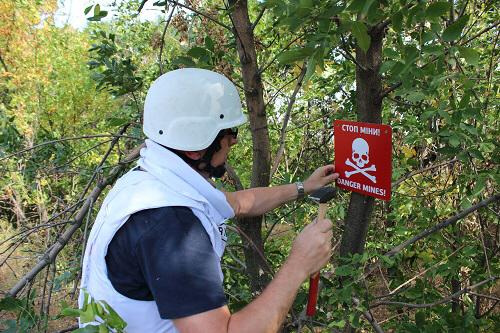 Member of International Committee of the Red Cross putting up signs warning of minefields near Berezove. Source