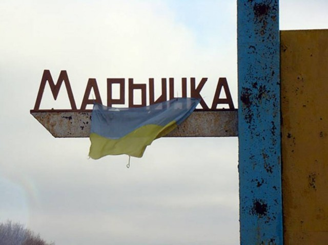 Ukrainian flag hanging from the town marker in Mar'inka