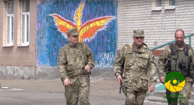 "Ukrainian Armed Forces at Stanytsia Luhanska in front of ""New Donbas"" Phoenix rising graffiti."