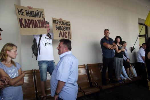 "Taras Polataiko at Chernivtsi train platform holding up signs: ""Stop killing the Carpathians"" and ""Stop exporting the forest!!"" Photo:"