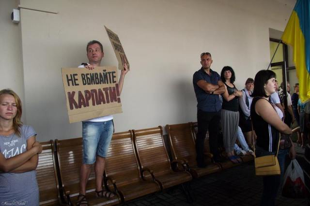 "Taras Polataiko on Chernivtsi train station platform holding a ""Don't kill the Carpathians"" sign. Photo:"