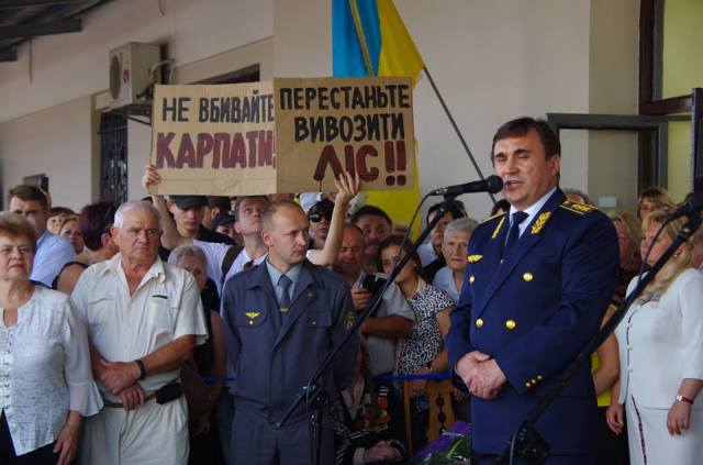 International artist Taras Polataiko flanked by police holding Carpathian Mountain deforestation protest signs while the Head of the Lviv Railway speaks during their 150th Anniversary celebrations on the train station platform September 8, 2016. Photo: