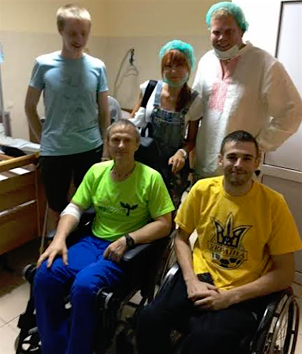 NODUS' ATO Ward 1: Volunteers Yuliya Grassby and James Clement visit wounded soldiers to talk about the war, their experiences and the future of Ukraine. Iliya Karpov (ATO volunteer participant/standing, suffered a brain trauma injury in January of 2015; he has had 3 rounds of rehabilitation at Nodus since February 2015 – was in a coma, then in a wheelchair, then used a cane – and this past summer, Iliya started his third round of rehabilitation to begin walking without a cane). Artur Kireev (officer, in yellow t-shirt) and Sergey Saliy (officer, in green t-shirt) were both wounded with spinal cord injuries. Artur graduated with a military degree. Sergey was a volunteer soldier.